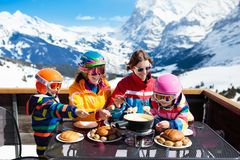 Family apres ski lunch in mountains. Skiing fun. Family with children enjoying apres ski lunch with traditional Swiss raclette and cheese fondue in restaurant on stock photo