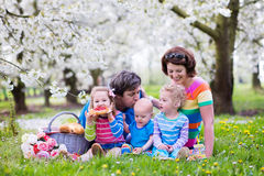 Family with children enjoying picnic in spring park Stock Image