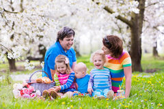 Family with children enjoying picnic in spring park Stock Images