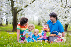 Family with children enjoying picnic in spring park Stock Photos