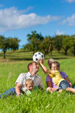 Family with children and football on a meadow. Family with two little boys playing in the grass on a summer meadow royalty free stock images