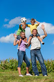 Family with children and football on a meadow Stock Images