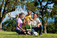 Family with children and football on a meadow. Family with two little boys playing in the grass on a summer meadow - they have a football royalty free stock photo