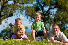 Family with children and football on a meadow. Family with two little boys playing in the grass on a summer meadow - they have a football royalty free stock photography