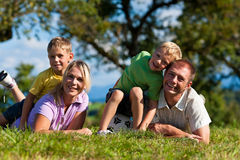 Family with children and football on a meadow. Family with two little boys playing in the grass on a summer meadow - they have a football royalty free stock photos