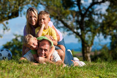 Family with children and football on a meadow Stock Photos