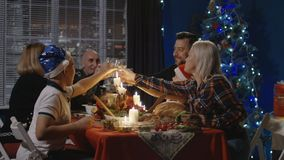 Reunited family having Christmas holiday celebration. Family with children and grandparents gathering at table at home having holiday feast on Christmas holiday stock footage