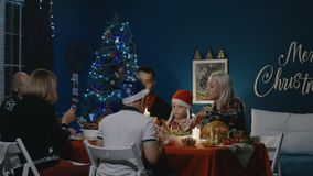 Reunited family having Christmas holiday celebration. Family with children and grandparents gathering at table at home having holiday feast on Christmas holiday stock video footage