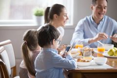 Family with children having breakfast in the kitchen. While whole family eating talking having breakfast, little preschool son in glasses holding using royalty free stock photography