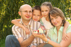 Family with children keeping wendy house in hands Royalty Free Stock Image