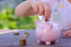 Piggy bank and little boy with coin on colorful background, close up. Family, children, money, investments and people concept - close up of father and daughter Royalty Free Stock Photos