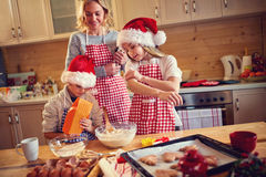 Family of children and mother baking cookies at home Royalty Free Stock Images