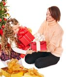 Family with children open gift box near Christmas tree. Royalty Free Stock Images