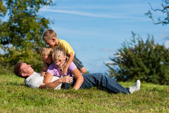 Family with children playing on a meadow. Happy family with two little boys playing in the grass on a summer meadow stock photo