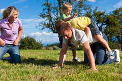 Family with children playing on a meadow. Happy family with two little boys playing in the grass on a summer meadow royalty free stock photos