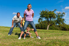 Family with children playing on a meadow Royalty Free Stock Images