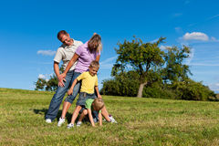 Family with children playing on a meadow. Happy family with two little boys playing in the grass on a summer meadow stock photography