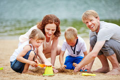 Family with children playing in sand of beach. Happy family with two children playing in sand of beach in summer Royalty Free Stock Photos