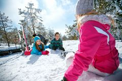 Family with children playing on snow at ski holiday in mountains. Happy family with children playing on snow at ski holiday in mountains Royalty Free Stock Photography