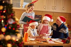 Family with children preparing cookies for Xmas royalty free stock photos