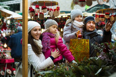 Family with children purchasing toys. Happy young family with children purchasing traditional Caga Tio toys at fair. Focus on woman Royalty Free Stock Image