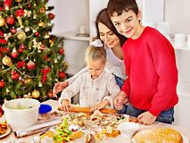 Family with children rolling dough in Xmas kitchen. Royalty Free Stock Photos