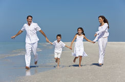 Family With Children Running Having Fun At Beach. A happy family of mother, father and two children, son and daughter, running holding hands and having fun in Stock Photos