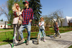 Family with children on scooters Royalty Free Stock Photography