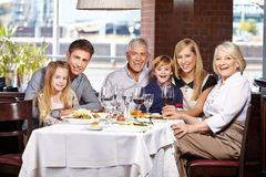 Family with children and seniors. Happy family with children and seniors eating out in a restaurant Royalty Free Stock Image