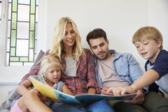Family With Children Sitting On Bed Reading Book Together Royalty Free Stock Image