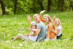 Family is sitting in the grass and waving friendly royalty free stock images