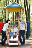 Family with children on slide outdoor. Stock Images