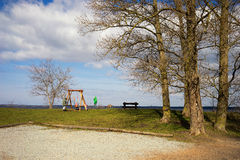 Family with children on a swing in the trees on a sunny spring d Stock Photos