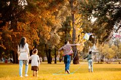 Family with children trying flying a kite in an. Autumn park royalty free stock photo