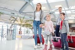 Family with children on the way to the connecting flight. At the stopover in the airport terminal stock image