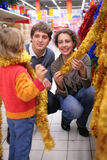 Family chooses Christmas-tree decoration royalty free stock photography