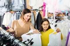 Family choosing dress in shop. Cheerful mother and daughter choosing pretty dress in children's cloths store Stock Images