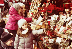 Family choosing floral decorations. Happy family of four choosing floral decorations at market. Focus on brunette girl Stock Image