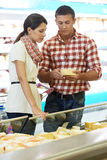 Family choosing food at shopping in supermarket. Young Family people choosing bio food cheese in grocery supermarket during weekly shopping Stock Image