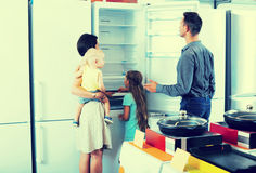 Family choosing new freezer in store. Young parents with two kids choosing new freezer in shop of household appliances Royalty Free Stock Photography