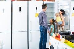 Family choosing new fridge. Spanish family with two children choosing new fridge in household store Royalty Free Stock Images