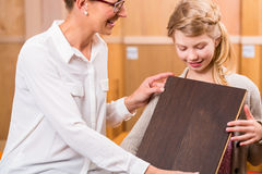 Family choosing parquet wood floor Royalty Free Stock Photos