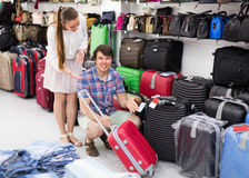 Family choosing suitcase with wheels. Happy family choosing a suitcase with wheels for their trip Stock Photography