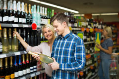 Family choosing wine at food shop Stock Image