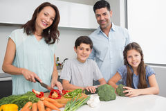 Family chopping vegetables in kitchen Royalty Free Stock Photography
