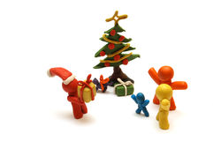 FAMILY CHRISTMAS. Plasticine figures staying together and celebrating christmas time, Santa Clous giving away presents Royalty Free Stock Photo
