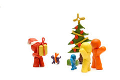 FAMILY CHRISTMAS. Plasticine figures staying together and celebrating christmas time, Santa Clous giving away presents Stock Photo