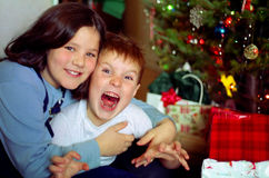 Family Christmas, Ontario Canada. Happy brother and sister under the tree with their Christmas presents stock photo