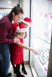 Family in Christmas attire looking at a display of wrist watch Royalty Free Stock Photo