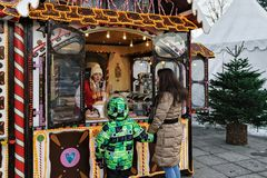 Family at Christmas candy house in Vilnius Lithuania. Vilnius, Lithuania - December 4, 2016: Family at Christmas candy house on Xmas market on Cathedral Square royalty free stock images